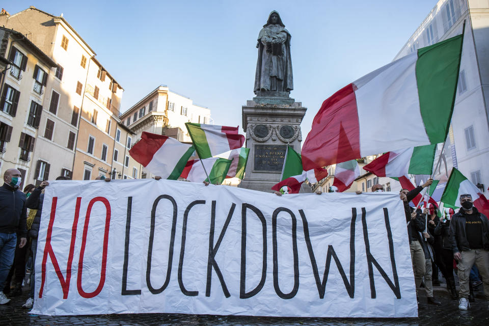 "Demonstrators wearing masks with the colors of the Italian flag wave flags and hold a banner with writing reading ""No Lockdown"" during a protest against the government's restriction measures to curb the spread of COVID-19, in Rome's Campo dei Fiori Square, Saturday, Oct. 31, 2020. (Roberto Monaldo/LaPresse via AP)"