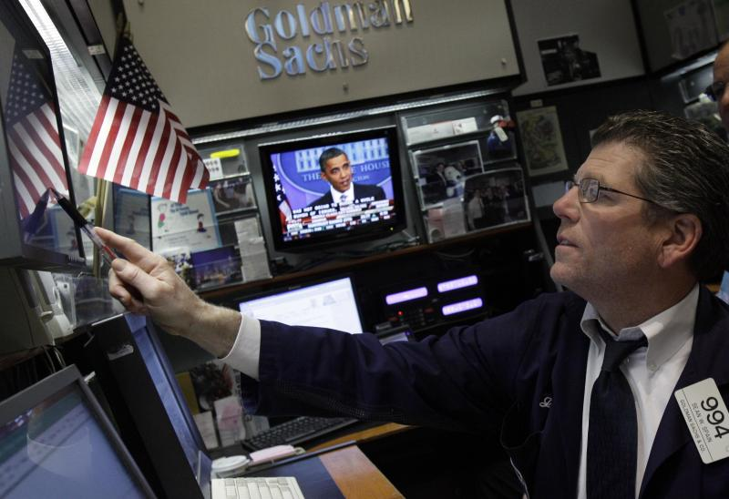 President Barack Obama is visible on a television screen as trader Sean Spain checks his screens in the Goldman Sachs booth on the floor of the New York Stock Exchange Tuesday, Dec. 7, 2010. (AP Photo/Richard Drew)