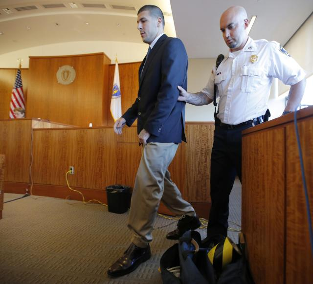 Aaron Hernandez, former player for the NFL's New England Patriots football team, is escorted from the witness stand after being questioned by Judge Susan Garsh during a court appearance at the Bristol County Superior Court in Fall River, Massachusetts October 9, 2013, in connection with the death of semi-pro football player Odin Lloyd in June. Hernandez, who was a rising star in the NFL before his arrest and release by the Patriots, has pleaded not guilty. REUTERS/Brian Snyder (UNITED STATES - Tags: CRIME LAW SPORT FOOTBALL)