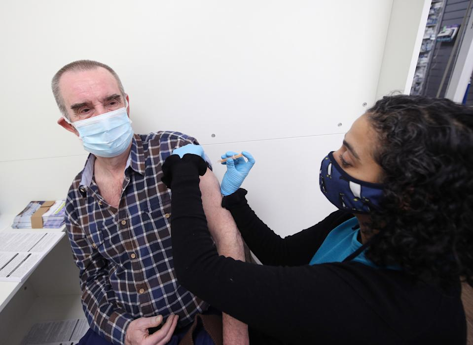 Pharmacist Asha Fowells vaccinates Barrie Reader, aged 74, with his first dose of the Oxford/AstraZeneca coronavirus vaccine, at Copes Pharmacy and Travel Clinic in Streatham, south London. Picture date: Thursday February 4, 2021.
