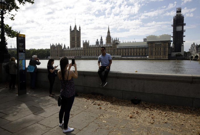 Tourists take photos near the Houses of Parliament in central London, Wednesday, Aug. 28, 2019. British Prime Minister Boris Johnson asked Queen Elizabeth II on Wednesday to suspend Parliament, throwing down the gauntlet to his critics and causing outrage among opposition leaders who will have even less time to thwart a no-deal Brexit. (AP Photo/Matt Dunham)