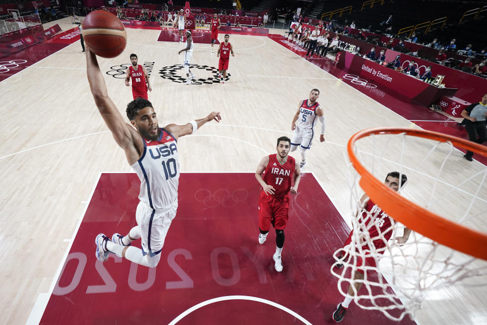 United States' Jayson Tatum (10) drives to the basket ahead of Iran's Navid Rezaeifar (17) during a men's basketball preliminary round game at the 2020 Summer Olympics, Wednesday, July 28, 2021, in Saitama, Japan. (Charlie Neibergall/Pool Photo via AP)