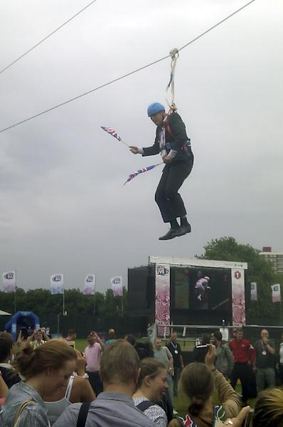 This mobile phone photo provided by Lee Medcalf shows Boris Johnson, the mayor of London, dangling in midair above the crowds at an open-air viewing site at east London's Victoria Park, on Wednesday, Aug. 1, 2012. (AP Photo/Lee Medcalf)