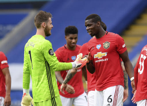Manchester United's goalkeeper David de Gea, left, celebrates with Manchester United's Paul Pogba at the end of the English Premier League soccer match between Leicester City and Manchester United at the King Power Stadium, in Leicester, England, Sunday, July 26, 2020. (Michael Regan/Pool via AP)