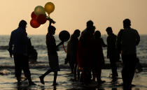 A boy sells balloons at a crowded Juhu beach in Mumbai, India, Saturday, Dec. 26, 2020. India's confirmed coronavirus cases have crossed 10 million with new infections dipping to their lowest levels in three months, as the country prepares for a massive COVID-19 vaccination in the new year. (AP Photo/Rafiq Maqbool)