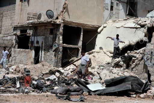 """Civilians search for personal belongings in the rubble of their house following shelling from Syrian government forces in the northern city of Aleppo on August 25. Syrian President Bashar al-Assad said on Sunday the foreign """"conspiracy"""" against his country would be defeated, as his forces were accused of a bloody rampage"""