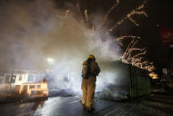 A firefighter extinguishes a a container that was set alight during protests against a nation-wide curfew in Rotterdam, Netherlands, Monday, Jan. 25, 2021. The Netherlands Saturday entered its toughest phase of anti-coronavirus restrictions to date, imposing a nationwide night-time curfew from 9 p.m. until 4:30 a.m. in a bid to control the COVID-19 infection rate. (AP Photo/Peter Dejong)