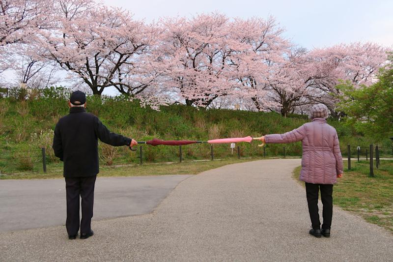 A good example of social distancing to avoid the spread of coronavirus (COVID-19). Two people (a man and a woman) stand apart holding two umbrellas.