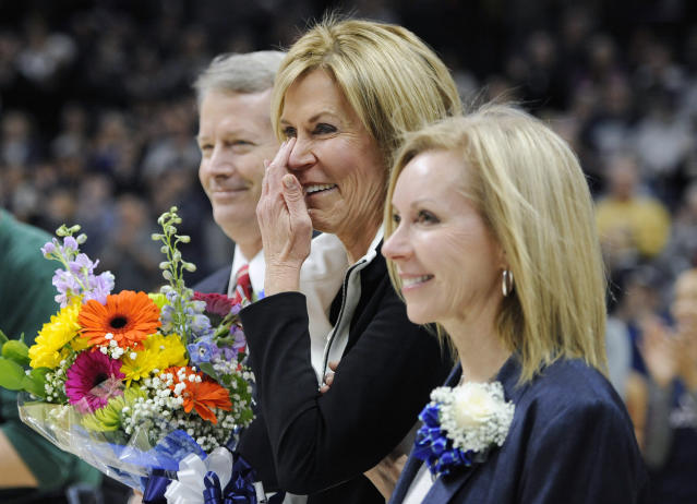 FILE - In this Feb. 27, 2016, file photo, Connecticut associate head coach Chris Dailey wipes a tear away as she stands with her family while a surprise unveiling of her name on the UConn Huskies of Honor wall prior to an NCAA college basketball game against Tulane, in Storrs, Conn. Connecticut assistant coach Chris Dailey and former Tennessee assistant Mickie DeMoss are breaking new ground this weekend when they get inducted into the Women's Basketball Hall of Fame. This marks the first time in the organization's 20-year history that it has inducted anyone based on accomplishments as an assistant coach.(AP Photo/Jessica Hill, File)