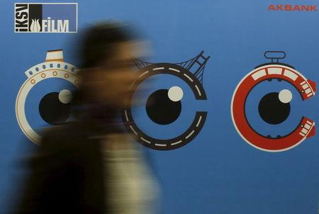 A woman walks past by a banner of Istanbul Film Festival at Atlas movie theatre in Istanbul