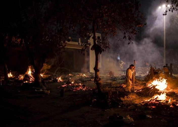 NEW DELHI, INDIA - APRIL 29: Workers can be seen at a crematorium where multiple funeral pyres are burning for patients who lost their lives to Covid-19 on April 29, 2021 in New Delhi, India. With recorded cases crossing 380,000 a day and 3000 deaths in the last 24 hours, India has more than 2 million active cases of Covid-19, the second-highest number in the world after the U.S. A new wave of the pandemic has totally overwhelmed the country's healthcare services and has caused crematoriums to operate day and night as the number of victims continues to spiral out of control. (Photo by Anindito Mukherjee/Getty Images)