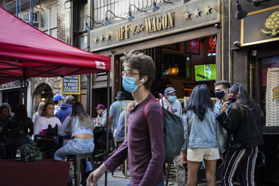 Diners sit outside restaurants offering outdoor service as part of continued COVID-19 economic impact mitigation efforts, Saturday, Oct. 3, 2020, in New York. (AP Photo/John Minchillo)