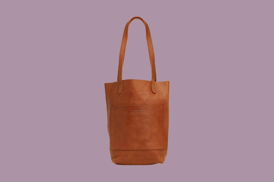 """<p>Ethically and sustainably made, this brown Ethiopian leather tote is sleek, stylish, and won't increase the size of your carbon footprint. Parker Clay works directly with farmers and the local agricultural market in Addis Ababa to keep money in the hands of the local farmers and businesses providing the materials. Additionally, their sister non-profit, <a href=""""https://www.elliltaproducts.com/"""" rel=""""nofollow noopener"""" target=""""_blank"""" data-ylk=""""slk:Ellilta"""" class=""""link rapid-noclick-resp"""">Ellilta</a>, helps them connect with woman fleeing the local sex work industry, so that they can provide them with high paying and sustainable jobs.</p> <p><strong><em>Shop Now: </em></strong><em>Parker Clay Caroline Tote, $198, </em><a href=""""https://www.parkerclay.com/collections/totes-bags/products/caroline-tote?variant=2125236535317"""" rel=""""nofollow noopener"""" target=""""_blank"""" data-ylk=""""slk:parkerclay.com"""" class=""""link rapid-noclick-resp""""><em>parkerclay.com</em></a><em>.</em></p>"""