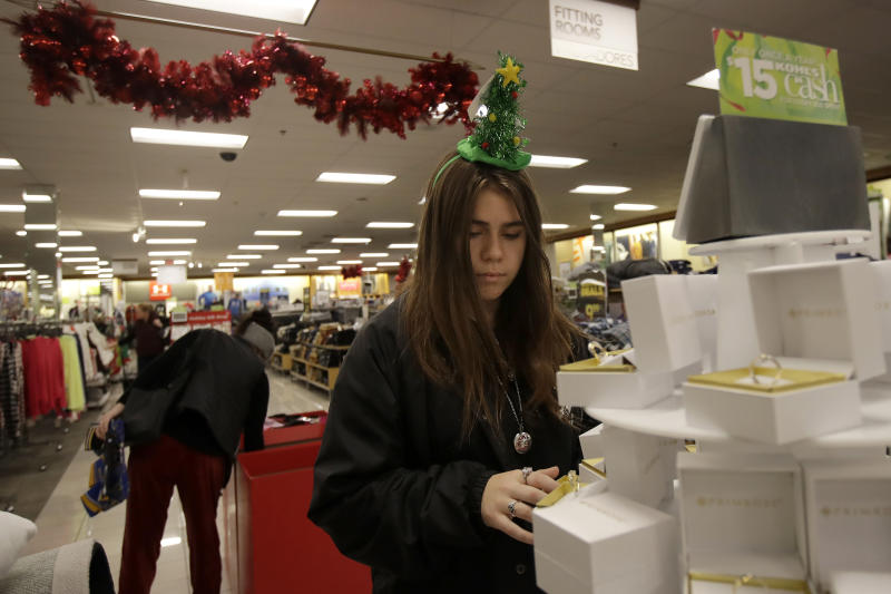 FILE - In this Nov. 29, 2019, file photo Daisy Clark shops at a Kohl's store in Colma, Calif. Holiday shopping doesn't end with Christmas. Bargain hunters can take advantage of fatter discounts on clothing, home decor and other items between Christmas and well into January. (AP Photo/Jeff Chiu, File)