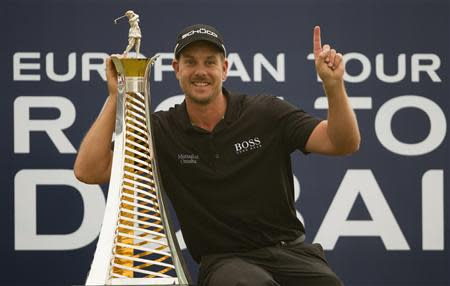 Henrik Stenson of Sweden poses with his 2013 Race to Dubai trophy after winning the DP World Tour Championship in Dubai November 17, 2013. World number three Stenson blasted a final round 64 to clinch the DP World Tour Championship on Sunday, also topping Europe's money list for 2013 after his six-stroke victory in the desert finale. REUTERS/Caren Firouz