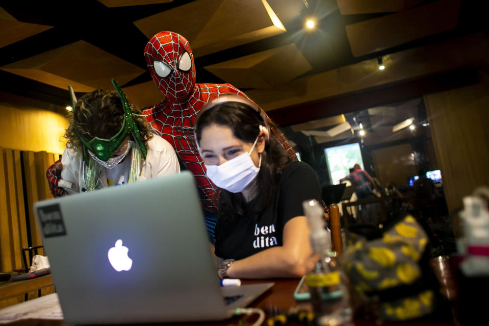 """Members of the """"Desliga da Justica"""" street band look at their production in Rio de Janeiro, Brazil, Sunday, Feb. 14, 2021. Their performance was broadcast live on social media for those who were unable to participate in the carnival due to COVID restrictions after the city's government officially suspended Carnival and banned street parades or clandestine parties. (AP Photo/Bruna Prado)"""