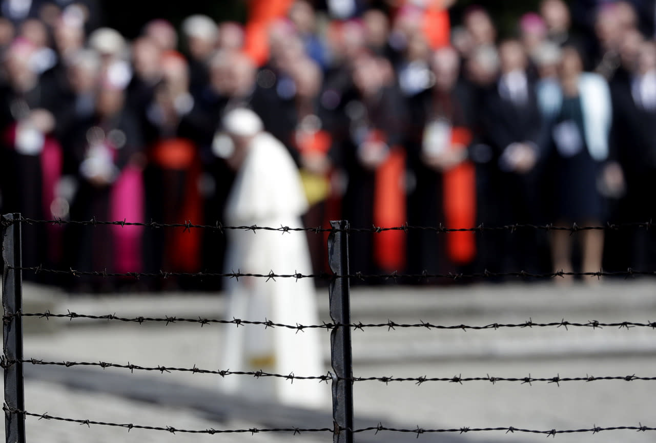 <p>Pope Francis, background, is framed by a barbed wire as he prays in front of the Memorial at the former Nazi Death Camp Auschwitz-Birkenau, in Oswiecim, Poland, July 29, 2016. (Photo: Gregorio BorgiaAP)</p>