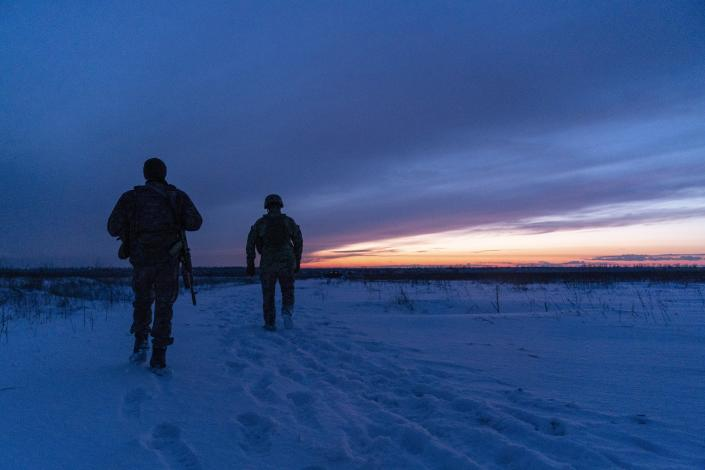 Ukrainian servicemen patrol an area after sunset near their position at the frontline near Vodiane, about 750 kilometers (468 miles) south-east of Kyiv, eastern Ukraine, Saturday, March 5, 2021. The country designated 14,000 doses of its first vaccine shipment for the military, especially those fighting Russia-backed separatists in the east. (AP Photo/Evgeniy Maloletka)