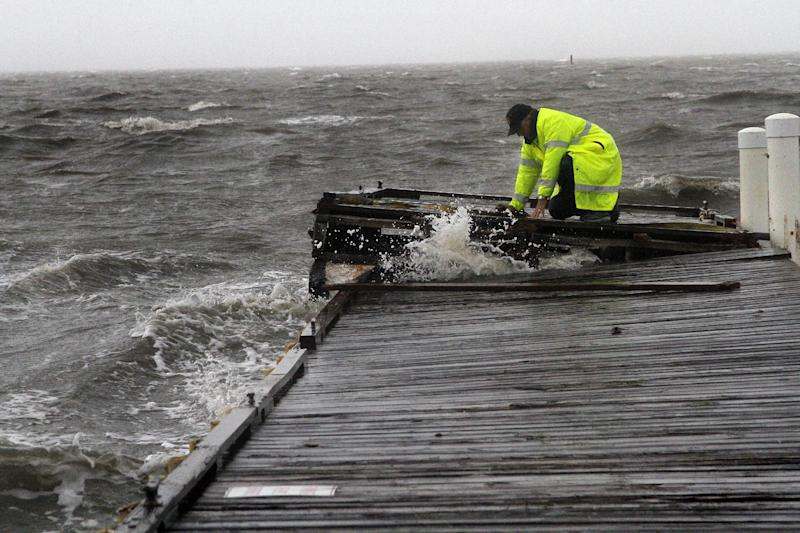 Cedar Key Police Chief Virgil Sandlin works on his hands an knees to secure a section of a floating dock as strong storm surge and flooding are felt from Tropical Storm Debby, in Cedar Key, Fla., Sunday, June 24, 2012. Sandlin said it was like riding a bronco trying to keep balance on the dock. Slow-moving Tropical Storm Debby's outer bands lashed Florida with rain and kicked up rough surf off Alabama on Sunday, prompting storm warnings for those states and causing at least one death. (AP Photo/The Gainesville Sun, Brad McClenny)
