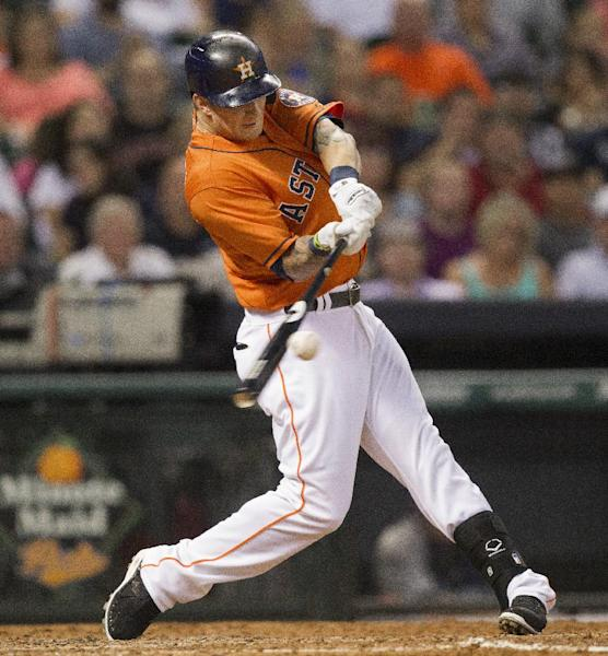 Houston Astros' Brandon Barnes hits a triple in the fourth inning against the Seattle Mariners in a baseball game Friday, July 19, 2013, in Houston. (AP Photo/Bob Levey)