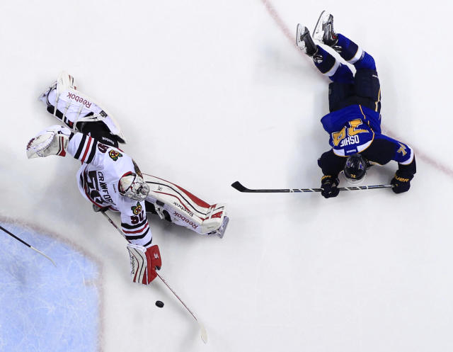 St. Louis Blues' T.J. Oshie, right, scores past Chicago Blackhawks goalie Corey Crawford during the second period in Game 5 of a first-round NHL hockey playoff series Friday, April 25, 2014, in St. Louis. (AP Photo/Jeff Roberson)