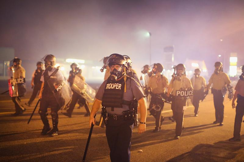 Police advance through a cloud of tear gas toward demonstrators protesting the killing of teenager Michael Brown, in Ferguson, Missouri, on August 17, 2014