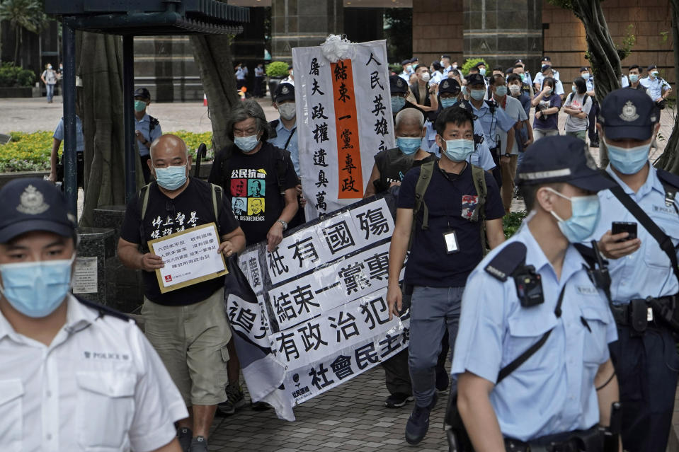 """Pro-democracy activists are surrounded by police officers as they march toward a flag raising ceremony in Hong Kong, Thursday, Oct. 1, 2020 to mark the China's National Day. The banner reads """" Stop One Party Ruling."""" (AP Photo/Kin Cheung)"""