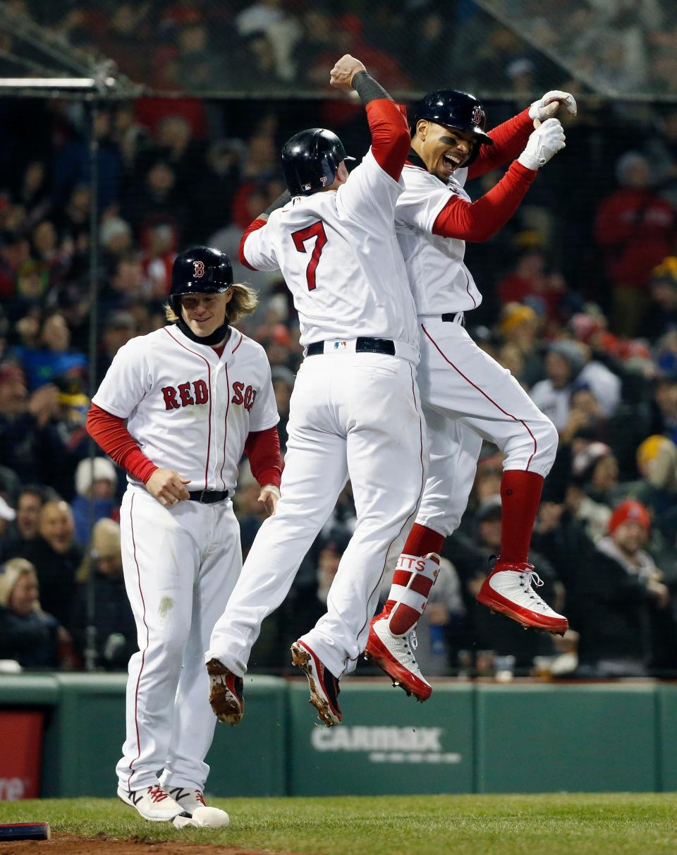 Boston Red Sox's Mookie Betts, right, celebrates with Christian Vazquez (7) and Brock Holt, left, after Betts' grand slam during the sixth inning of a baseball game against the New York Yankees in Boston, Tuesday, April 10, 2018. (AP Photo/Michael Dwyer)