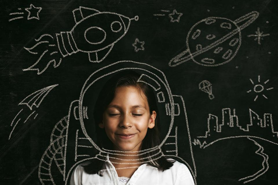 Young girl dreaming of flying to space. Illustrative concept.
