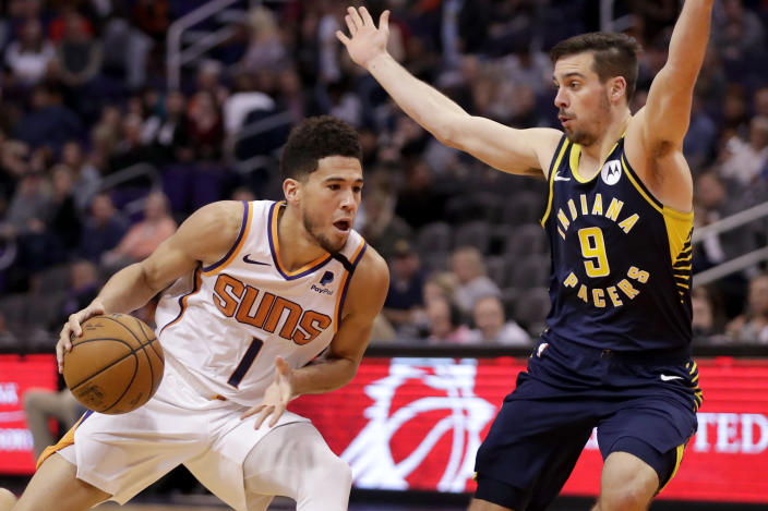 Phoenix Suns guard Devin Booker (1) drives as Indiana Pacers guard T.J. McConnell (9) defends during the second half of an NBA basketball game, Wednesday, Jan. 22, 2020, in Phoenix. (AP Photo/Matt York)