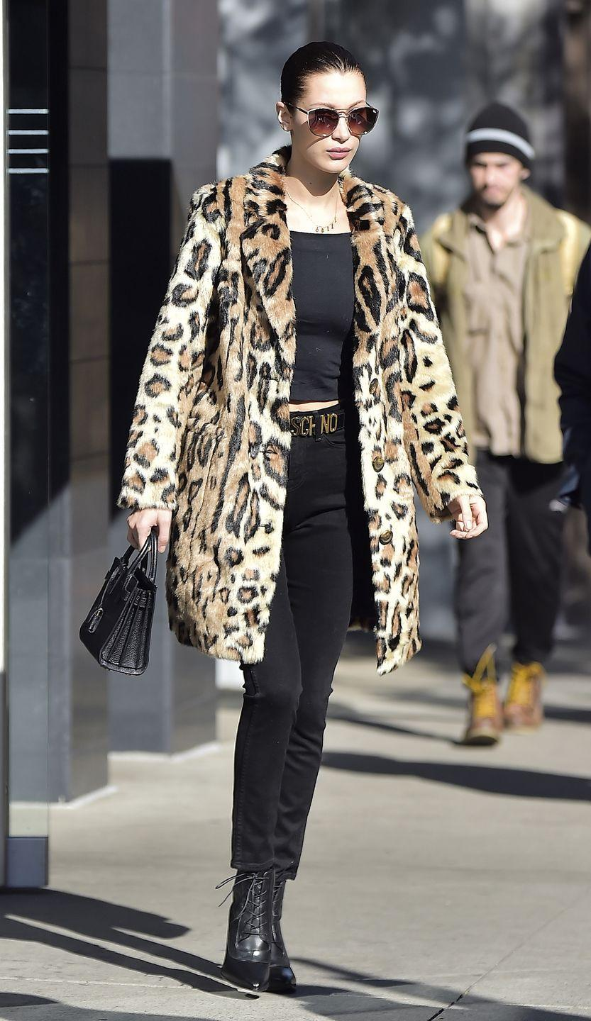 <p>Bella pairs her statement leopard coat with an all-black outfit: a tee, high-waisted jeans, Moschino belt, tinted sunglasses by Quay, Stuart Weitzman booties and a handbag, while out in NYC. </p>