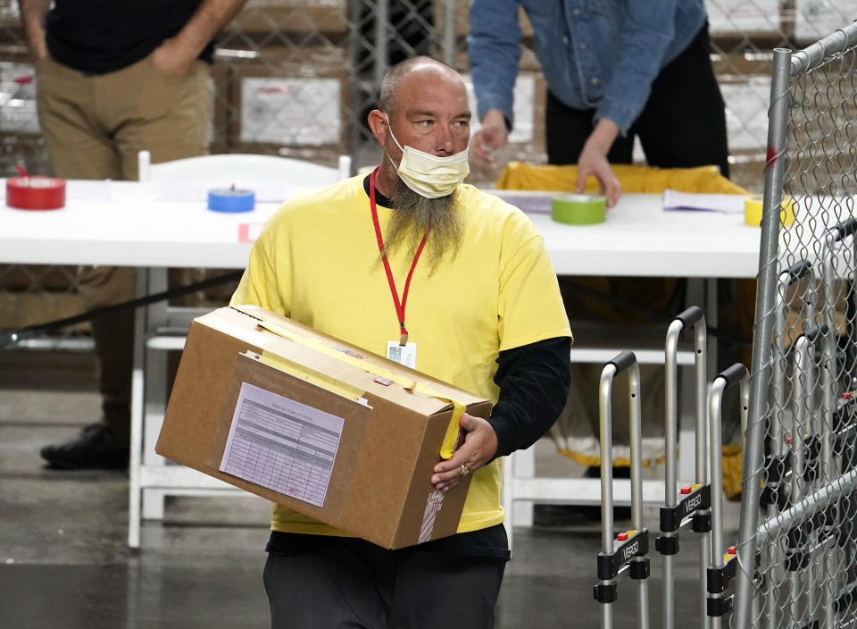 A box of Maricopa County ballots cast in the 2020 general election are delivered to be examined and recounted by contractors working for Florida-based company, Cyber Ninjas, who was hired by the Arizona State Senate at Veterans Memorial Coliseum in Phoenix, Thursday, April 29, 2021. (Rob Schumacher/The Arizona Republic via AP, Pool)