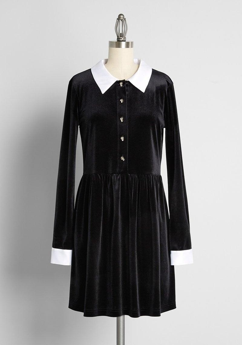 <p>How cute is this Wednesday Addams-inspired <span>Is It Wednesday Yet? Mini Dress</span> ($69)? After all, a black velvet dress is perfect for the fall and winter seasons. The white collar and cuffs give this dress vintage vibes. </p>