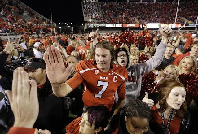 Utah quarterback Travis Wilson (7) receives high-fives a fan after Utah defeated Stanford 27-21 during an NCAA college football game on Saturday, Oct. 12, 2013, in Salt Lake City. (AP Photo/Rick Bowmer)