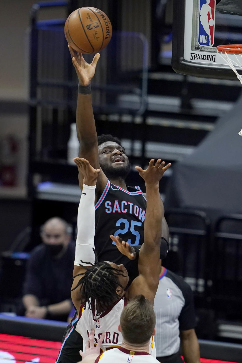 Sacramento Kings forward Chimezie Metu (25) shoots as Cleveland Cavaliers forward Isaac Okoro, middle, and forward Dean Wade defend during the first half of an NBA basketball game in Sacramento, Calif., Saturday, March 27, 2021. (AP Photo/Jeff Chiu)
