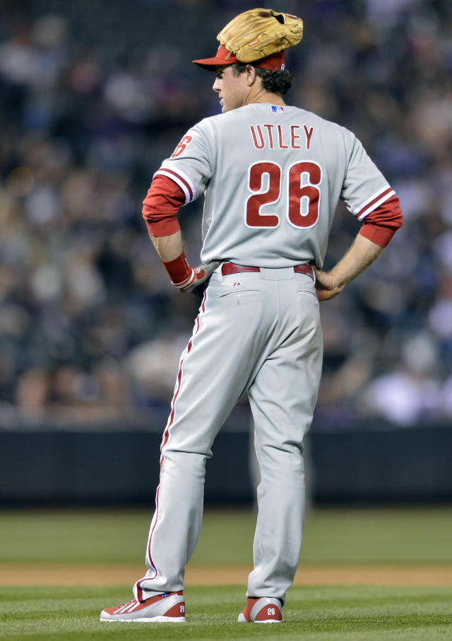 Philadelphia Phillies second baseman Chase Utley wears his glove on his head while waiting for a pitching change against the Colorado Rockies during the seventh inning of a baseball game on Friday, April 18, 2014, in Denver. (AP Photo/Jack Dempsey)