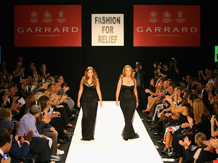 Princess Beatrice and Sarah Ferguson walk on a runway in a fashion show.