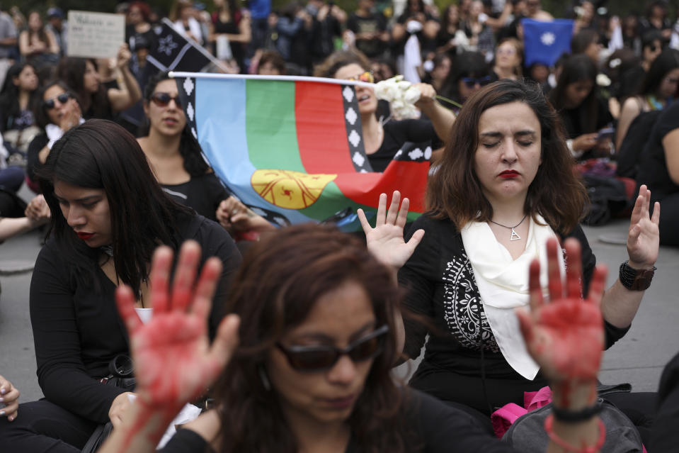 Women sit in front of La Moneda presidential palace during a march against President Sebastian Pinera in Santiago, Chile, Friday, Nov. 1, 2019. Groups of Chileans continued to protests as government and opposition leaders debated the response to nearly two weeks of protests that have paralyzed much of the capital and forced the cancellation of two major international summits. (AP Photo/Rodrigo Abd)
