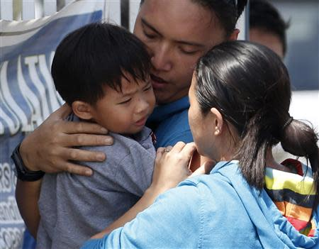 A two-year-old boy who was freed along with dozens of residents taken hostage for a week by the Muslim rebels of Moro National Liberation Front (MNLF) is reunited with his parents, at a police camp in Zamboanga city in southern Philippines September 17, 2013. REUTERS/Erik De Castro