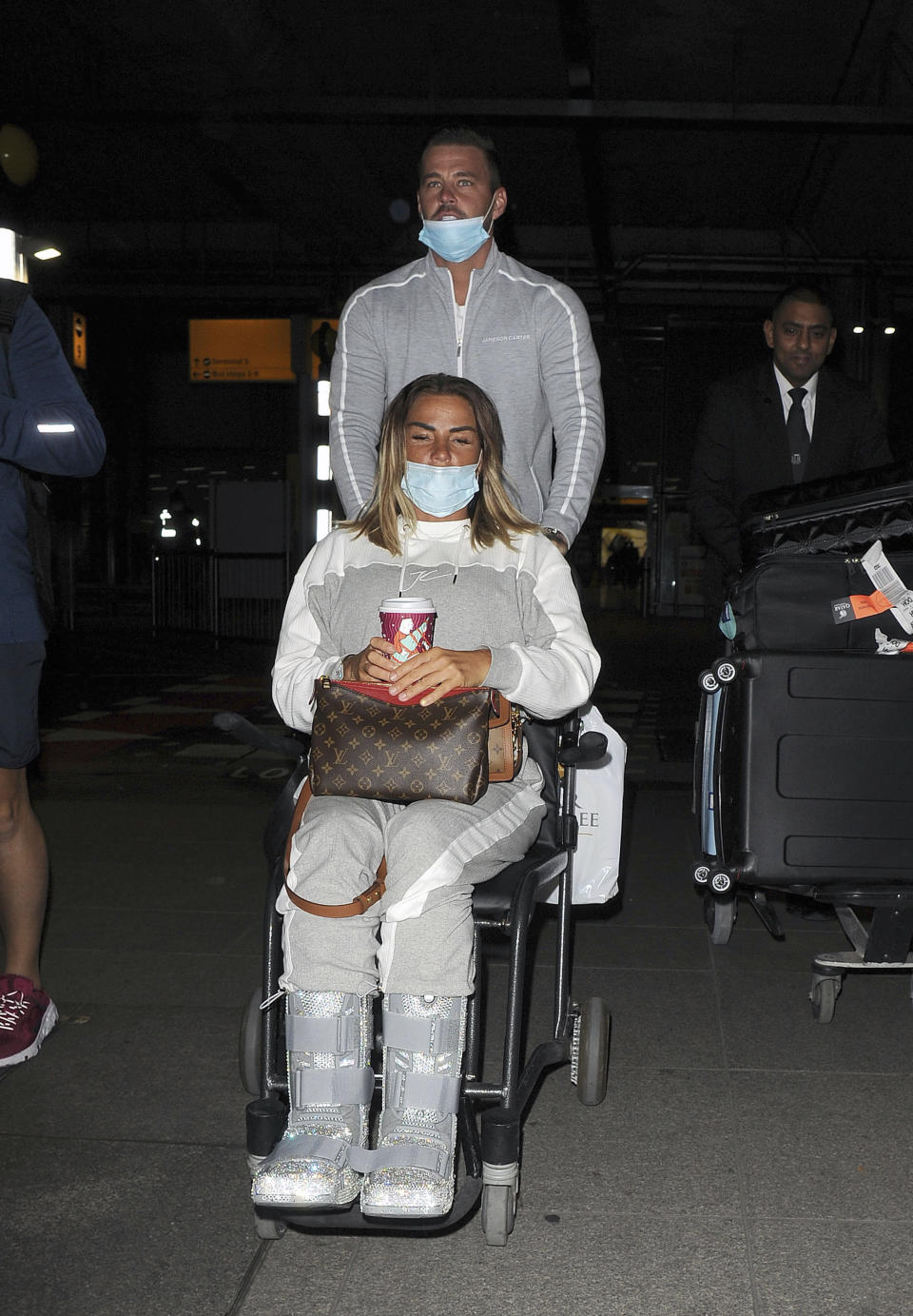 Photo by: zz/KGC-305/STAR MAX/IPx 2020 11/6/20 Katie Price and her boyfriend Carl Woods are seen on November 6, 2020 arriving at Heathrow Airport - returning to England from their holiday in The Maldives. They were not in compliance with strict government guidelines mandated during the worldwide coronavirus pandemic as they both were wearing their face masks improperly as both had their noses exposed. (London, England, UK)