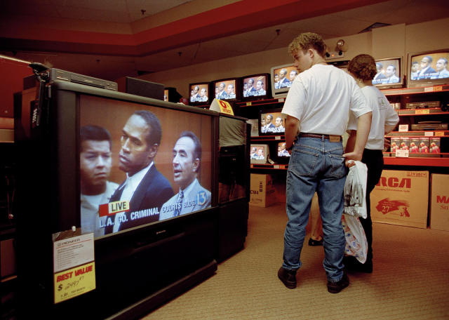 <p>The nation continued to be transfixed by the Simpson saga. Mall shoppers in Tampa, Fla.,watch banks of televisions in an electronics store, June 20, 1994, as O.J. Simpson was arraigned in Los Angeles, Calif., for the alleged murder of his ex-wife and her male friend. Simpson, standing with his attorney Robert Shapiro, right, pled innocent to murder charges. (Photo: Chris O'Meara/AP) </p>