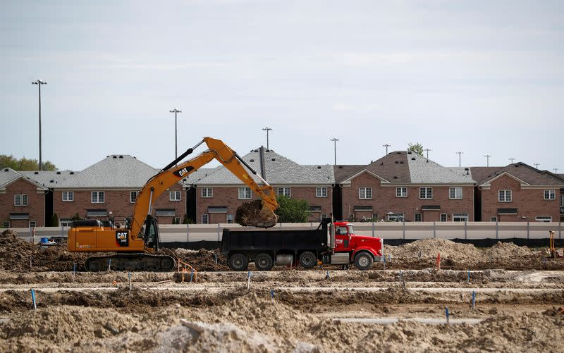 FILE PHOTO: Construction workers build homes on a lot in Toronto