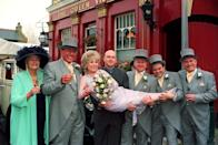 EastEnders stars Barbara Windsor (who plays bride 'Peggy Mitchell') and Mike Reid (groom 'Frank Butcher', sceond from left), with co-stars during a photocall outside the Queen Vic pub at London's Elstree studios, where their on-screen wedding reception was filmed. * Joined by fellow actors (l-r) Pam St Clement (Pat), Ross Kemp (Grant), Steve McFadden (Phil), Shaun Williamson (Barry), and Tony Caunter (Roy). (Photo by John Stillwell - PA Images/PA Images via Getty Images)