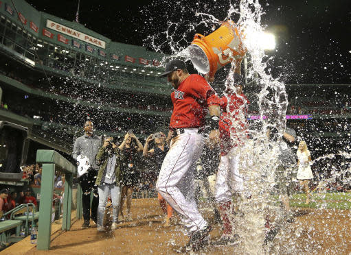 Boston Red Sox's J.D. Martinez is doused after the team's baseball game against the Seattle Mariners at Fenway Park, Friday, June 22, 2018, in Boston. Martinez singled in the go-ahead run in the Red Sox's 14-10 victory. (AP Photo/Elise Amendola)
