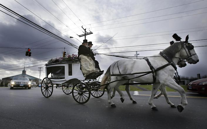 A horse drawn carriage carrying the body of Anna Grace Marquez-Greene leaves the church after her funeral in Bloomfield, Conn., Saturday, Dec. 22, 2012. Marquez-Greene, 6, was killed when gunman Adam Lanza opened fire at Sandy Hook Elementary School last week, killing 26 people, including 20 children, before killing himself. (AP Photo/Seth Wenig)(AP Photo/Seth Wenig) (AP Photo/Seth Wenig)