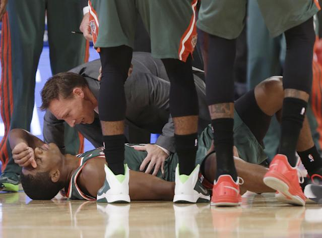 A trainer helps Milwaukee Bucks' Brandon Knight after he was hurt on a play during the first half of an NBA basketball game against the New York Knicks on Wednesday, Oct. 30, 2013, in New York. (AP Photo/Frank Franklin II)