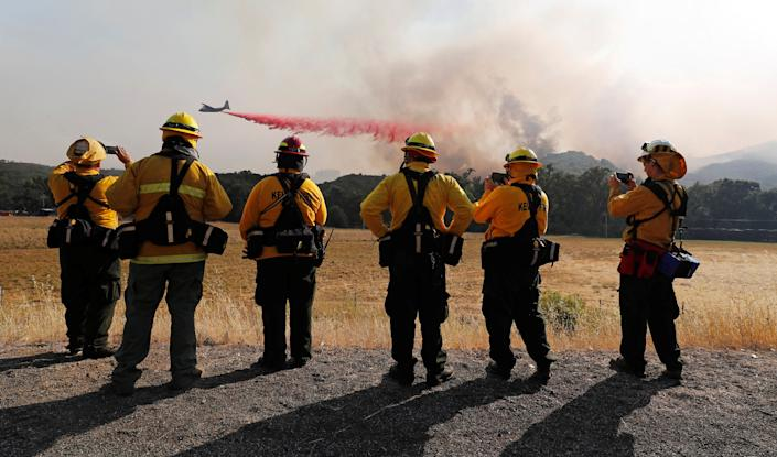 Firefighters watch as an air tanker drops fire retardant to protect homes along the crest of a hill at the River Fire near Lakeport, California.