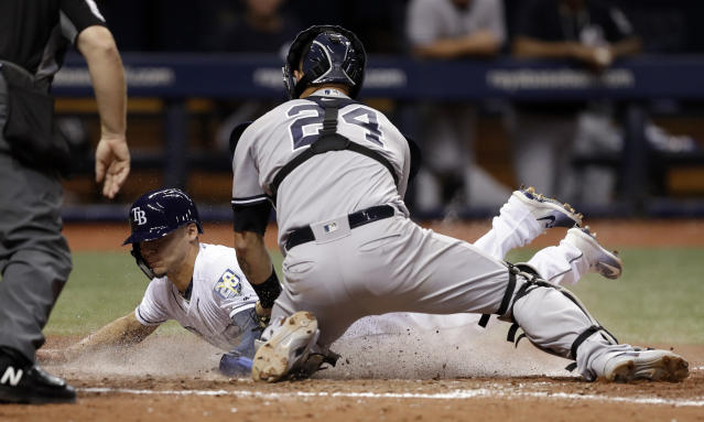 Tampa Bay Rays' Andrew Velazquez scores ahead of the tag by New York Yankees catcher Gary Sanchez (24) during the eighth inning of a baseball game Wednesday, Sept. 26, 2018, in St. Petersburg, Fla. (AP Photo/Chris O'Meara)