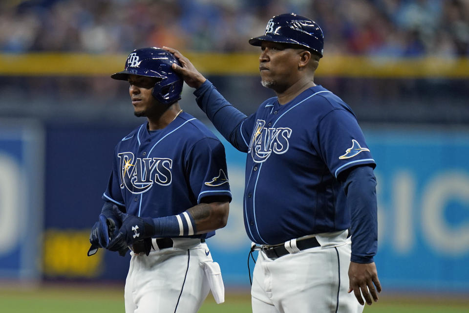Tampa Bay Rays' Wander Franco, left, gets a pat on the helmet from first base coach Ozzie Timmons after Franco drew a walk from Boston Red Sox starting pitcher Eduardo Rodriguez on his first major league at-bat during the first inning of a baseball game Tuesday, June 22, 2021, in St. Petersburg, Fla. (AP Photo/Chris O'Meara)