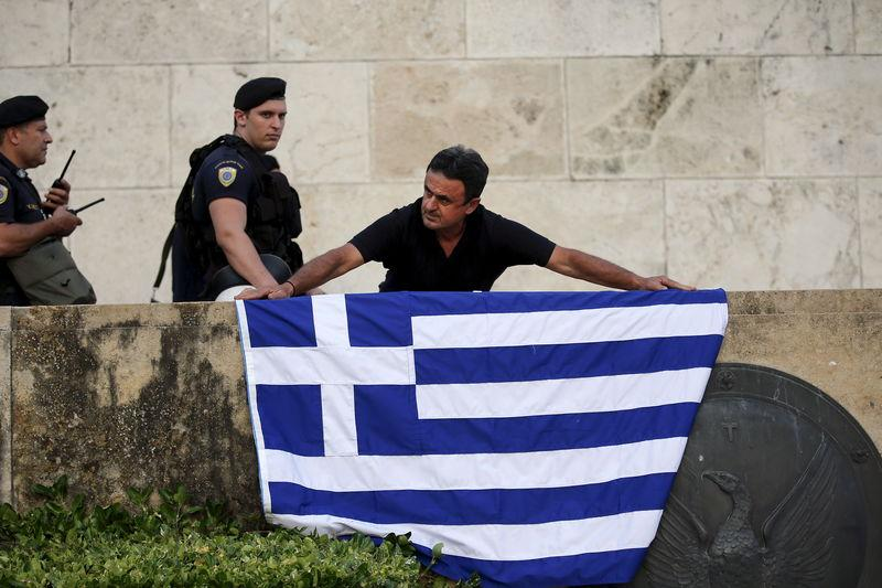 An anti-EU protester unfurls a Greek national flag next to riot police on the steps in front of the parliament building during a demonstration of about five hundred people in Athens, Greece July 13, 2015. REUTERS/Jean-Paul Pelissier